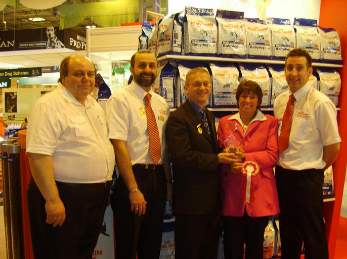 GLYNIS & COLIN ON THE ROYAL CANIN STAND AT CRUFTS 2007 BEING PRESENTED WITH THE TOP STUD IN BREED AWARDED TO OSCAR