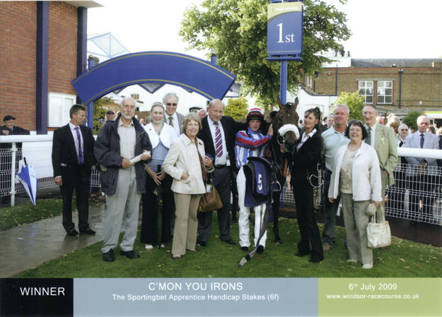 members in the winning enclosure after 'IRONS' wins again at WINDSOR